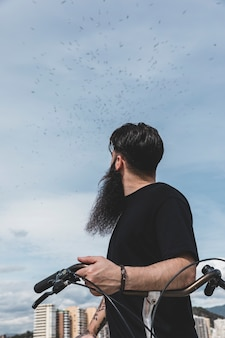 Primer plano de un hombre joven con bicicleta mirando bandada de pájaros volando en el cielo