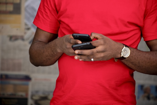 Primer plano de un hombre joven con dos teléfonos en una habitación