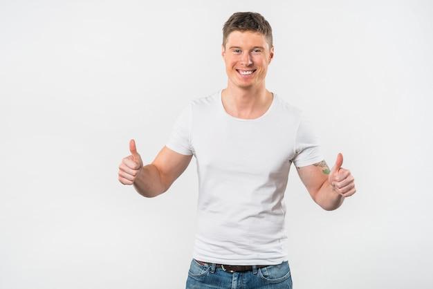 Primer plano de un hombre joven feliz que muestra el pulgar hacia arriba signo sobre fondo blanco