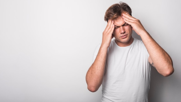 Primer plano de un hombre joven que sufre de dolor de cabeza aislado sobre fondo blanco