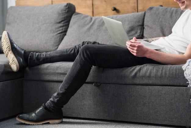 Primer plano de un hombre joven sentado en el sofá mirando portátil