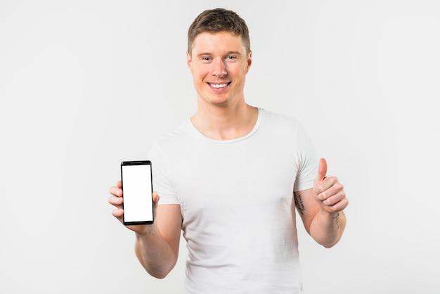 Primer plano del hombre joven sonriente que sostiene el móvil en la mano que muestra el pulgar hacia arriba signo