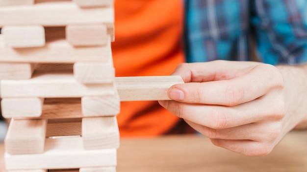 Primer plano de un hombre jugando a la torre de bloques de madera juego