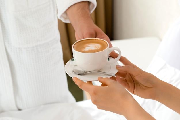 Primer plano de un hombre llevando café a su novia acostada en la cama
