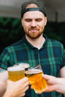 Primer plano, de, hombre, llevando, gorra, brindar, vasos de cerveza, con, amigos