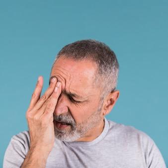 Primer plano de un hombre maduro que sufre de dolor de cabeza sobre fondo azul