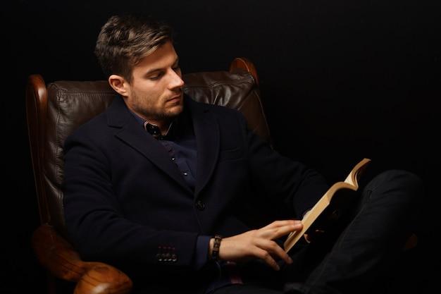 Primer plano de un hombre maduro en traje elegante sentado en un sofá de cuero y libro de lectura
