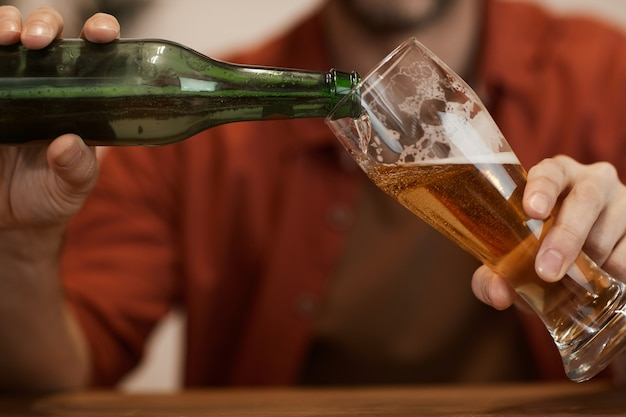 Primer plano de hombre maduro vertiendo la cerveza de la botella en el vaso