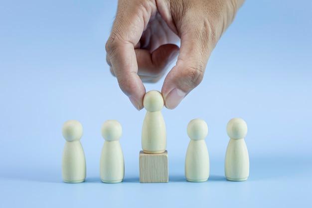 Primer plano el hombre de la mano elige el mejor modelo de liderazgo de equipo de personas exitosas sobre fondo azul.