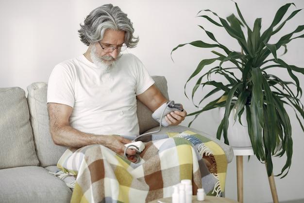 Primer plano de un hombre mayor de 70 a 75 años midiendo la presión. hombre para medir su presión arterial. salud y cuidados.