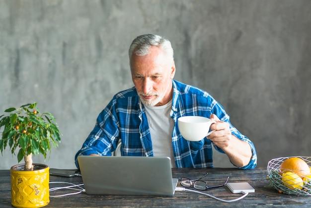 Primer plano de un hombre mayor que sostiene la taza de café usando la computadora portátil cargada con el banco del poder