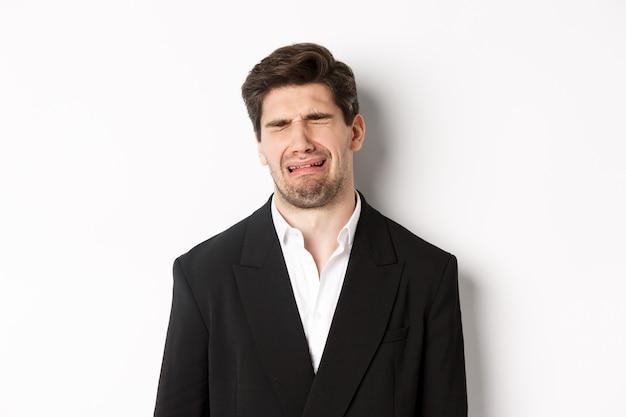 Primer plano de un hombre miserable en traje, llorando y sollozando, sintiéndose triste, de pie contra el fondo blanco.