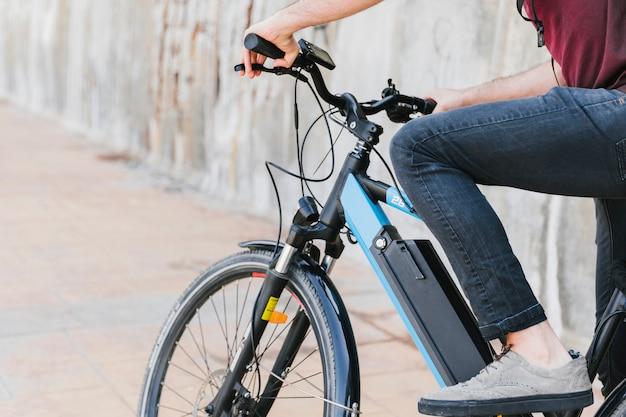 Primer plano de un hombre montado en una bicicleta eléctrica