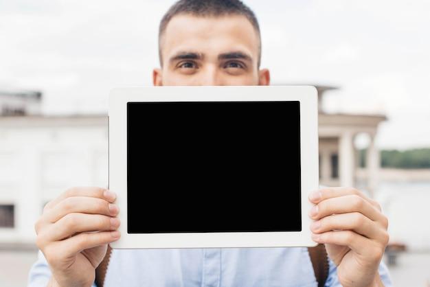 Primer plano del hombre mostrando tableta digital al aire libre