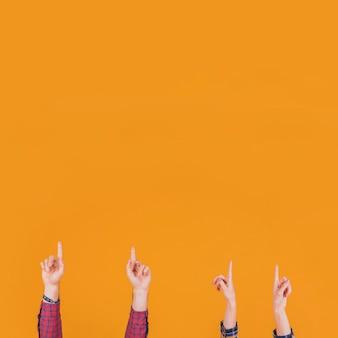 Primer plano de un hombre y una mujer apuntando con su dedo hacia arriba sobre un fondo naranja