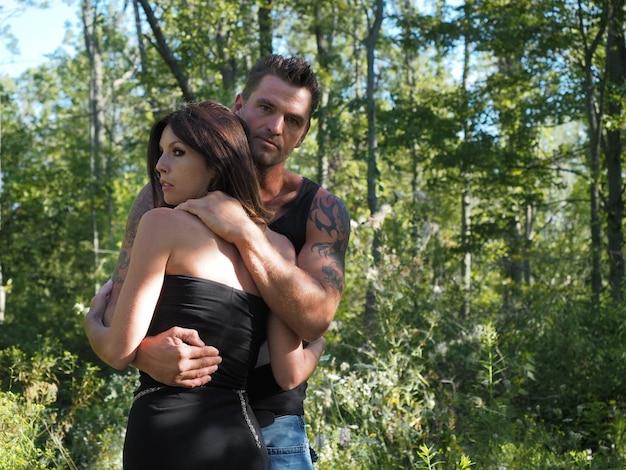 Primer plano de un hombre musculoso sosteniendo firmemente a una mujer