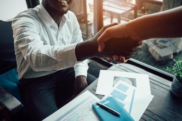 Primer plano de un hombre de negocios africano y un hombre asiático dándose la mano mientras está sentado en la cafetería