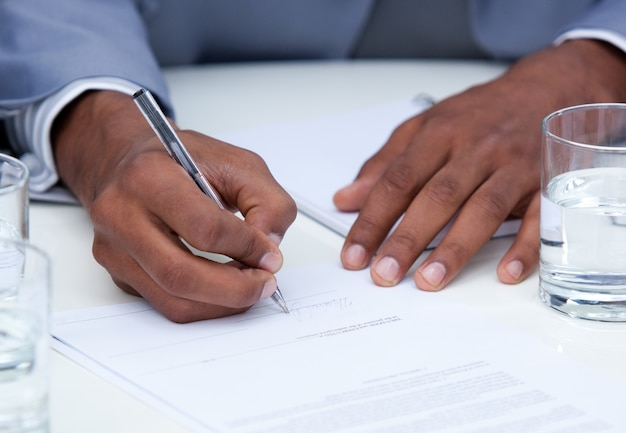 Primer plano del hombre de negocios ambicioso que firma un contrato