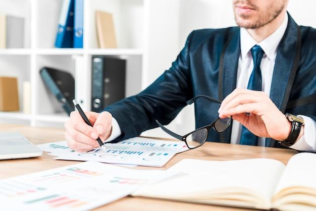 Primer plano de un hombre de negocios analizando el gráfico con anteojos en la mano