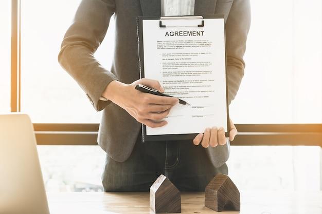 Primer plano de hombre de negocios apuntando y firmando un acuerdo para la compra de casa. concepto del encargado del banco.