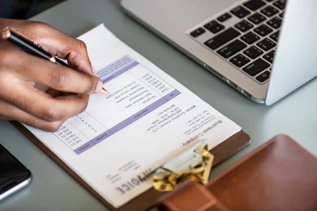 Primer plano de hombre de negocios comprobando el papel de la factura fiscal