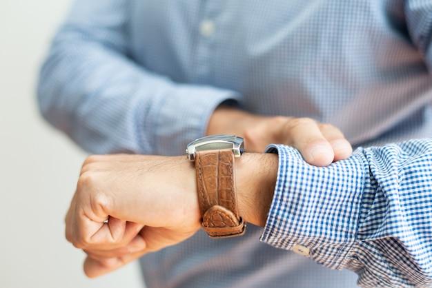 Primer plano de hombre de negocios control de tiempo en el reloj