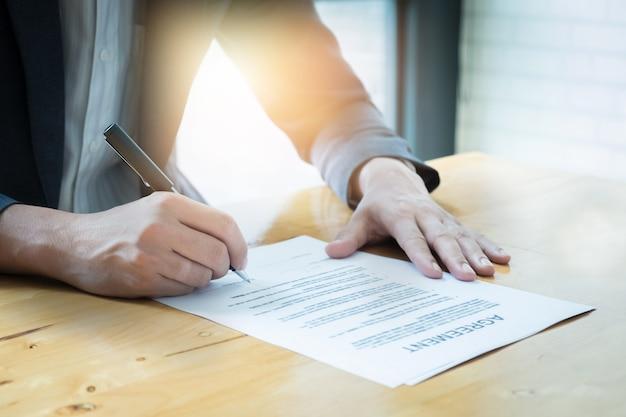 Primer plano de hombre de negocios la firma de acuerdo en el contrato.