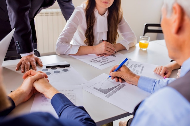 Primer plano de hombre de negocios maduro analizando el gráfico con sus colegas