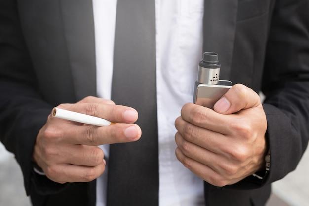 Primer plano de un hombre de negocios mantenga cigarrillo electrónico en la mano