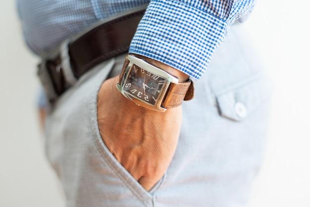 Primer plano de hombre de negocios manteniendo la mano en el bolsillo de los pantalones