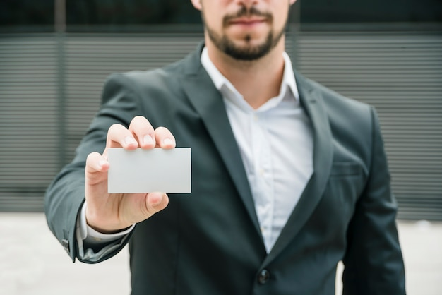 Primer plano de un hombre de negocios de pie al aire libre que muestra la tarjeta de visita blanca en blanco