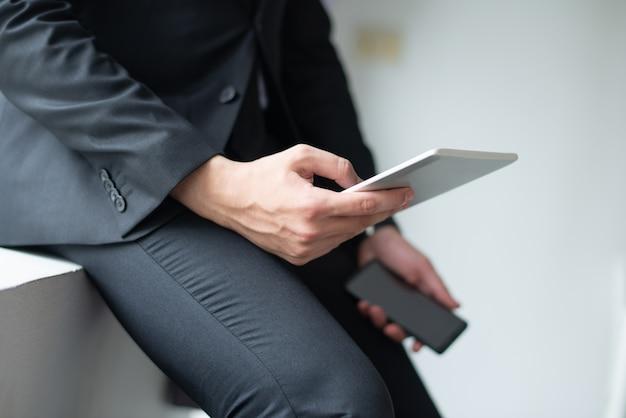 Primer plano de hombre de negocios usando gadgets y apoyándose en el alféizar