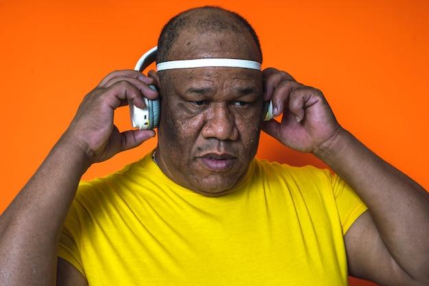 Primer plano de un hombre negro y de nacionalidad afroamericana que está escuchando música en sus auriculares