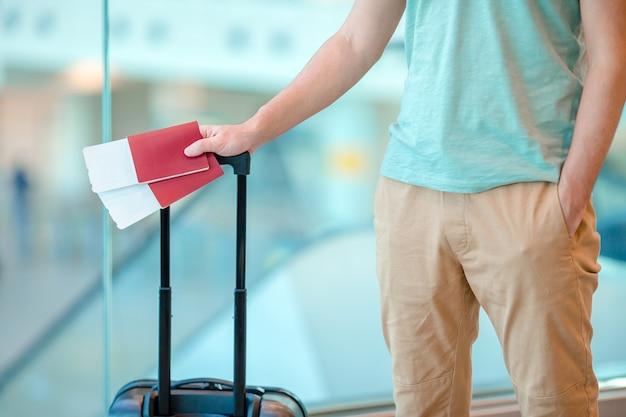 Primer plano de hombre con pasaportes y tarjeta de embarque en el aeropuerto