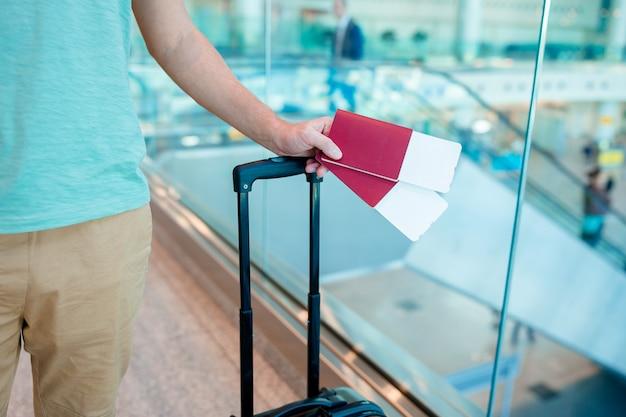 Primer plano del hombre con pasaportes y tarjeta de embarque en el aeropuerto