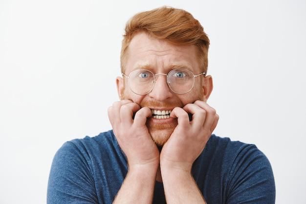 Primer plano de hombre pelirrojo asustado inseguro en gafas mordiéndose las uñas asustado