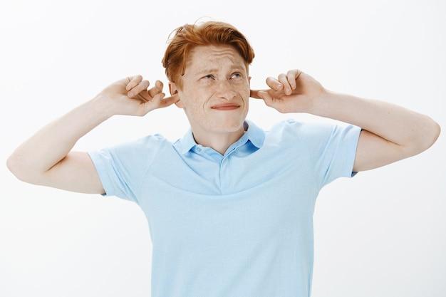 Primer plano de hombre pelirrojo disgustado y reacio que cierra los oídos con los dedos, molesto con vecinos ruidosos