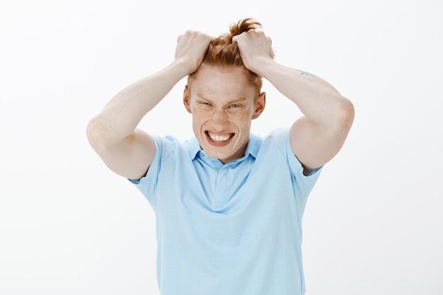 Primer plano de hombre pelirrojo enojado indignado arrancando el pelo de la cabeza