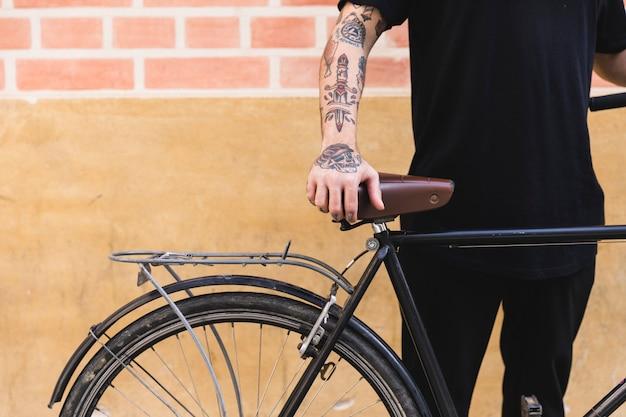 Primer plano de un hombre de pie con la bicicleta delante de la pared