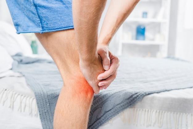 Primer plano de un hombre de pie cerca de la cama que sufre de dolor en la rodilla