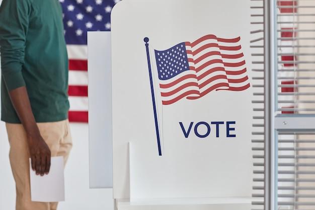 Primer plano del hombre de pie cerca de las urnas en el colegio electoral que va a votar