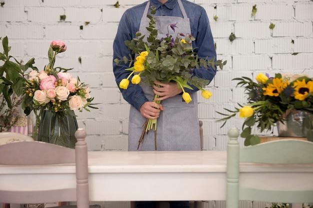 Primer plano de un hombre de pie detrás de la mesa con ramo de flores en la mano