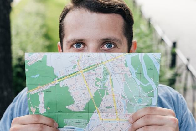 Primer plano del hombre que cubre su boca con el mapa