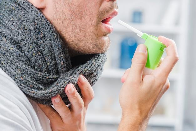 Primer plano de un hombre que lleva una bufanda gris alrededor de su cuello con un spray para tratar el dolor de garganta
