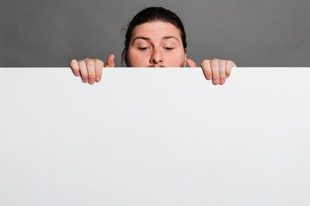 Primer plano de un hombre que mira a escondidas detrás de la tarjeta blanca de papel contra el fondo gris