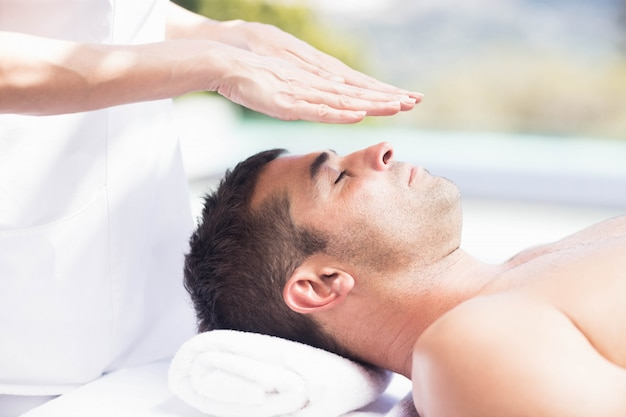 Primer plano del hombre que recibe un masaje de cabeza de masajista en un spa