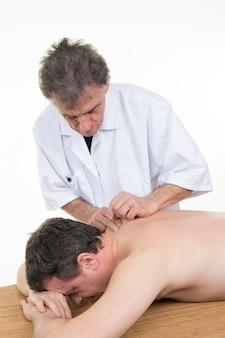 Primer plano de un hombre que recibe tratamiento de acupuntura en el centro de belleza spa