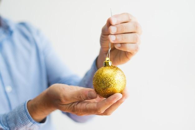 Primer plano del hombre que sostiene la bola de navidad brillante