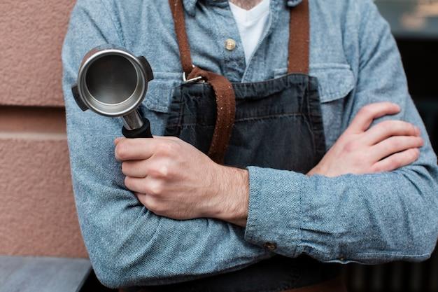 Primer plano del hombre que sostiene el componente de la máquina de café