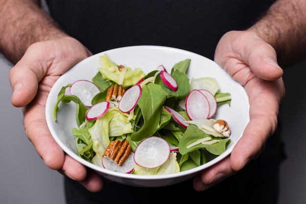 Primer plano del hombre que sostiene un tazón de ensalada en las manos